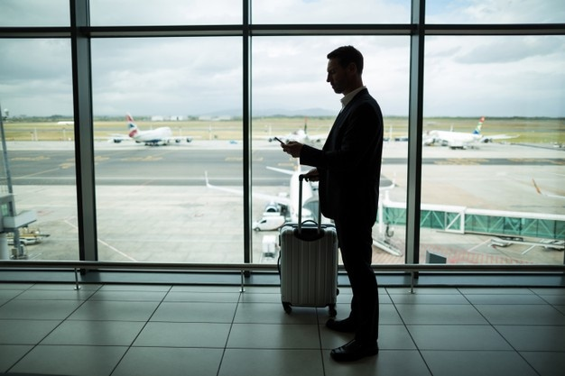 businessman with luggage and his phone in an airport