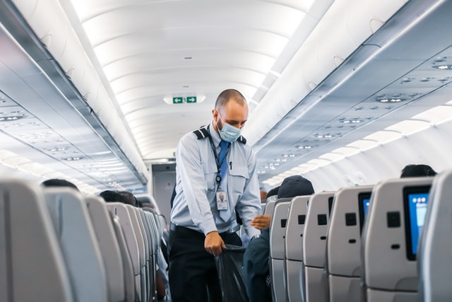 airatendant with mask inside an airplane