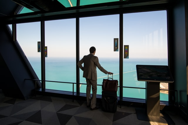 Man with luggages looks through the window in an airport (Business Travel Tips)